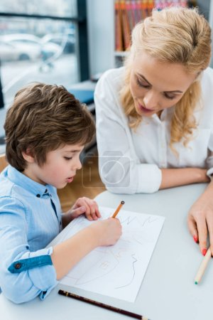Photo pour Selective focus of woman looking at cute child drawing on paper - image libre de droit