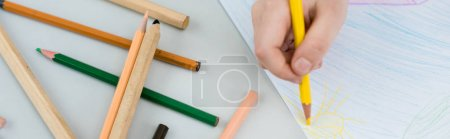 Photo for Panoramic shot of kid drawing with yellow pencil on paper - Royalty Free Image