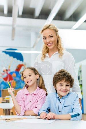 Photo pour Foyer sélectif de l'enfant gai retenant des crayons de couleur près du garçon et de la femme attirante - image libre de droit