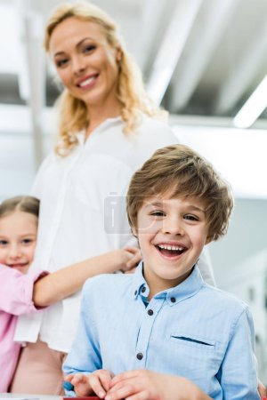 Foto de Selective focus of cheerful kid smiling while looking at camera near woman - Imagen libre de derechos