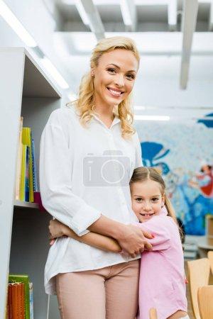 Foto de Happy and cute kid standing and hugging attractive woman - Imagen libre de derechos