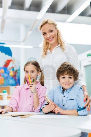 Foto de Selective focus of cute kids holding color pencils and sitting near happy woman - Imagen libre de derechos