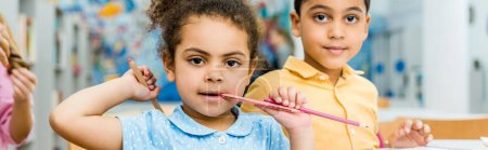 Photo pour Panoramic shot of cute african american kid biting pencil near adorable child - image libre de droit