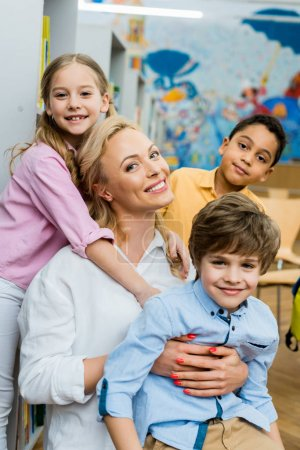 Photo for Cheerful kid hugging attractive woman near multicultural boys - Royalty Free Image