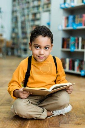 joyeux garçon afro-américain assis sur le sol et tenant livre