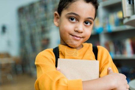 adorable afroamericano niño sosteniendo libro y mirando la cámara
