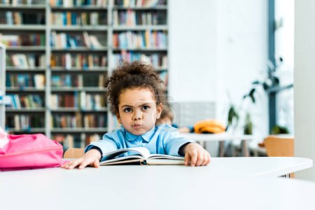 Photo for Bored african american kid sitting near book in library - Royalty Free Image