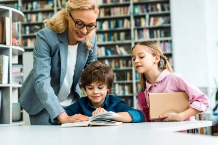 Photo pour Professeur joyeux dans des lunettes debout près des enfants mignons lecture livre dans la bibliothèque - image libre de droit