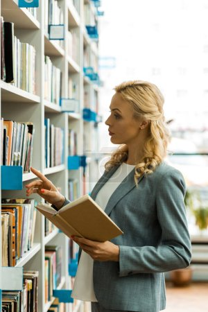 Photo pour Femme blonde attirante faisant des gestes près de l'étagère tout en retenant le livre - image libre de droit