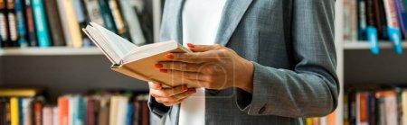 Photo pour Prise de vue panoramique de la femme tenant le livre tout en se tenant dans la bibliothèque - image libre de droit