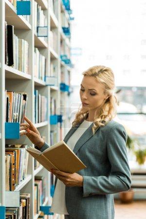 Photo pour Belle blonde femme lecture livre tandis que debout dans la bibliothèque - image libre de droit