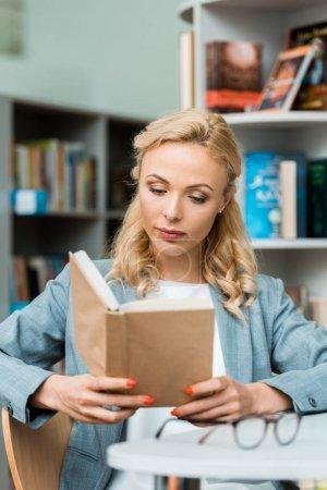 Photo pour Femme blonde attirante et focalisée s'asseyant dans la bibliothèque et le livre de lecture - image libre de droit