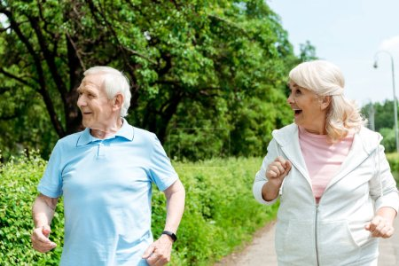 Photo for Happy senior man and retired woman running in park - Royalty Free Image