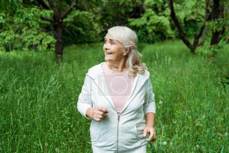 Photo for Happy senior woman with grey hair running in green park - Royalty Free Image