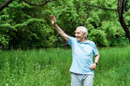 Photo pour Homme âgé joyeux avec les cheveux gris agitant la main dans le parc - image libre de droit