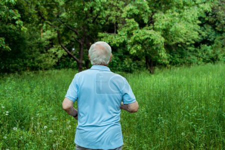 Photo for Back view of retired man in sportswear standing in park - Royalty Free Image