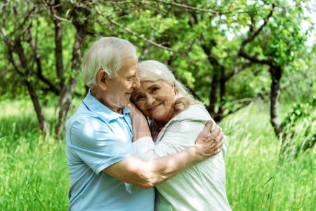 Photo pour Cheerful senior man hugging happy wife with grey hair - image libre de droit