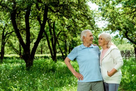 Photo for Cheerful senior man standing with hand on hip near wife with hand in pocket - Royalty Free Image