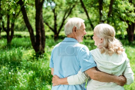 Photo for Smiling pensioner hugging happy senior wife while standing in green park - Royalty Free Image