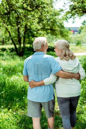 Photo for Cheerful pensioner hugging happy senior wife in green park - Royalty Free Image
