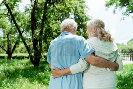 Photo for Back view retired man hugging senior happy wife in green park - Royalty Free Image