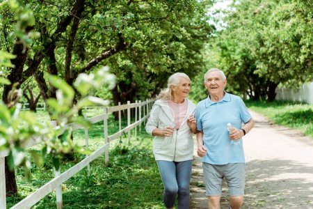Photo for Selective focus of cheerful retired man running near senior wife in park - Royalty Free Image