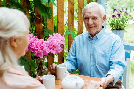 Photo for Selective focus of happy senior man holding hands with wife - Royalty Free Image