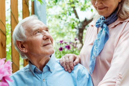 cropped view of cheerful retired woman standing near happy senior husband