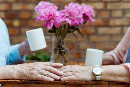 Photo for Cropped view of senior man touching hand of retired woman - Royalty Free Image