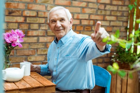 Photo pour Selective focus of happy senior man pointing with finger while holding cup - image libre de droit