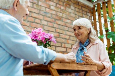 Photo pour Vue d'angle bas de la femme aînée gaie regardant le mari retraité - image libre de droit