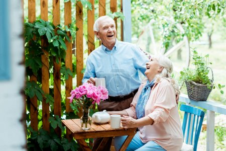 Photo for Selective focus of happy senior man laughing with cheerful wife near pink flowers - Royalty Free Image