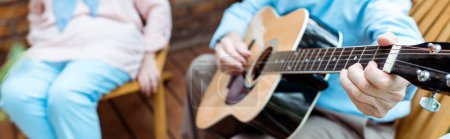 Photo for Panoramic shot of senior man playing acoustic guitar near wife - Royalty Free Image