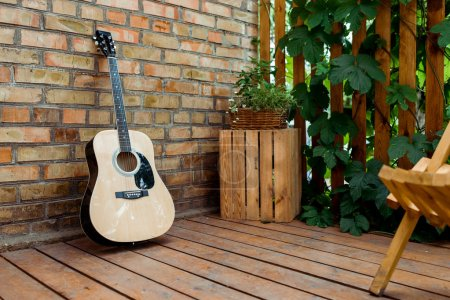Photo for Selective focus of acoustic guitar near brick wall and wooden fence with green leaves - Royalty Free Image