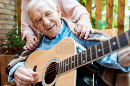 Photo for Cropped view of senior woman near happy retired husband playing acoustic guitar - Royalty Free Image