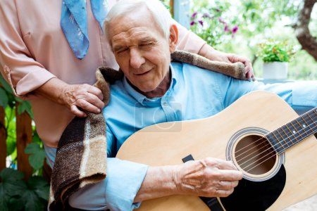 Photo for Cropped view of senior woman standing near happy retired husband playing acoustic guitar - Royalty Free Image