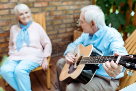 Photo for Selective focus of retired husband playing acoustic guitar near wife - Royalty Free Image