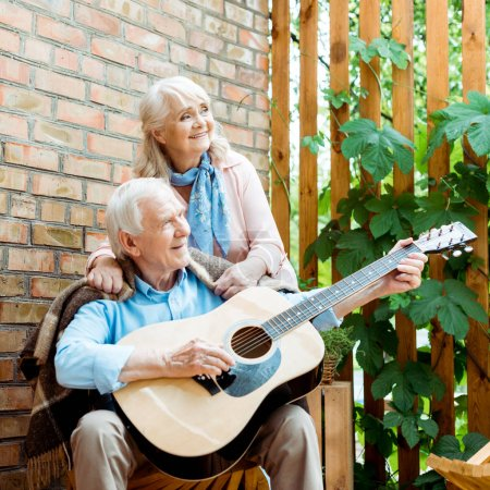 Photo pour Happy retired husband playing acoustic guitar near senior wife - image libre de droit