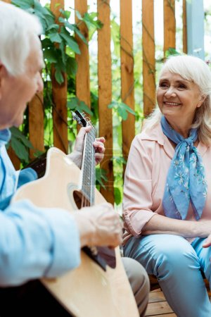 Photo for Selective focus of happy retired woman looking at husband playing acoustic guitar - Royalty Free Image