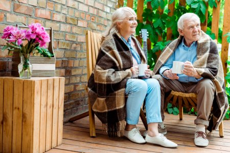 cheerful senior woman and man sitting on terrace and holding cups