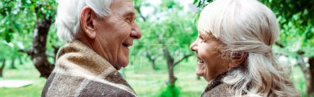 Photo for Panoramic shot of senior husband looking at happy retired wife in plaid blanket - Royalty Free Image