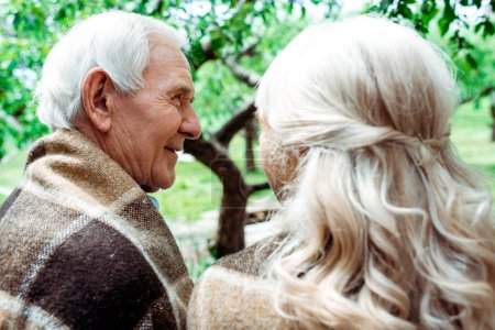 Photo for Selective focus of smiling senior man in plaid blanket near wife - Royalty Free Image
