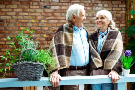 happy pensioners smiling while standing in plaid blankets near flower pots