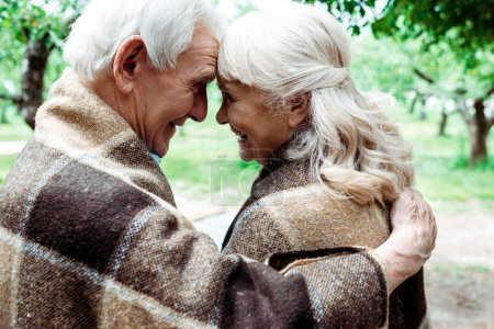 Photo for Happy senior woman and man in blankets looking at each other - Royalty Free Image