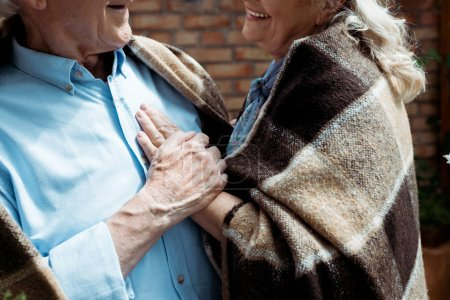 Photo for Cropped view of happy retired woman touching senior husband in plaid blanket - Royalty Free Image