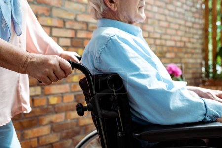 Photo for Cropped view of senior disabled man sitting in wheelchair near wife - Royalty Free Image