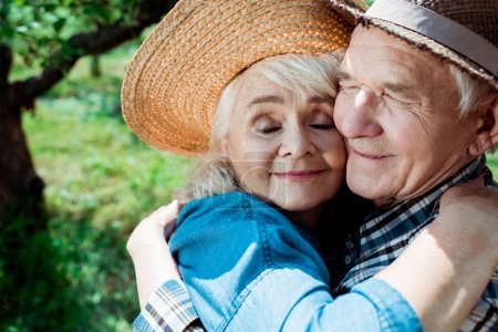Photo for Cheerful senior woman hugging happy retired husband with closed eyes - Royalty Free Image