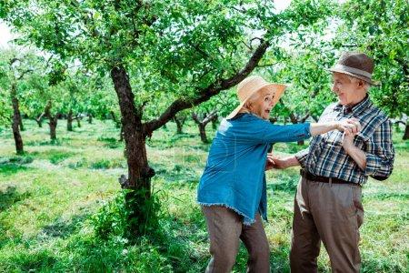 Photo pour Heureuse femme retraitée tenant la main avec son mari tout en se tenant près des arbres - image libre de droit