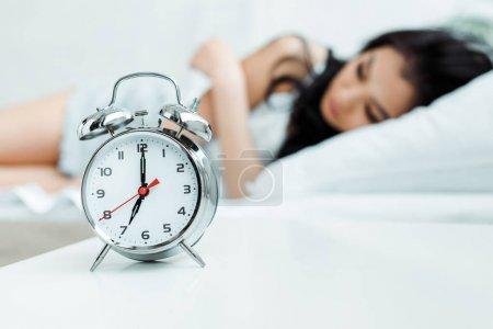 Photo pour Foyer sélectif du réveil rétro près de la jeune fille endormie - image libre de droit