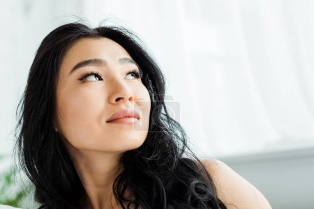 Photo pour Low angle view of pensive and attractive thai woman - image libre de droit